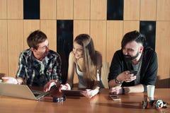 Groupe d'amis se tenant prêt la table dans la grands salle et regard à l'écran de l'ordinateur portable Photos libres de droits