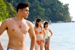 Groupe d'amis se tenant prêt le regard de plage à l'extérieur à Photo stock