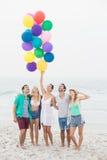 Groupe d'amis se tenant sur la plage avec des ballons Photo stock