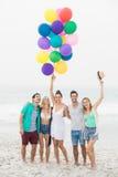 Groupe d'amis se tenant sur la plage avec des ballons Photos stock