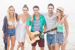 Groupe d'amis se tenant sur la plage avec une guitare Image libre de droits