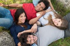 Groupe d'amis se trouvant sur l'herbe Image libre de droits