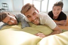 Groupe d'amis se trouvant sur le plancher dans un bureau vide Photos stock