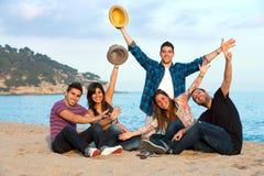 Groupe d'amis soulevant des mains sur la plage. Photographie stock