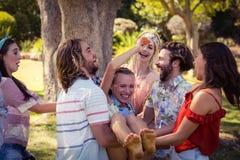 Groupe d'amis soulevant la femme au terrain de camping Photos stock