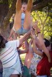 Groupe d'amis soulevant la femme au terrain de camping Images libres de droits