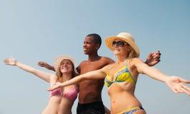 Groupe d'amis souriant à la plage Image stock