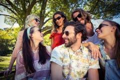 Groupe d'amis souriant en parc Image stock
