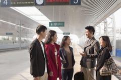 Groupe d'amis souriant et parlant sur la plate-forme ferroviaire Photos libres de droits