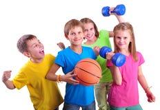 Groupe d'amis sportifs d'enfants avec les haltères et la boule Photo stock