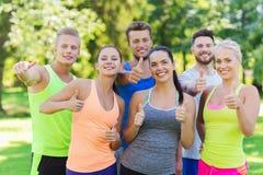 Groupe d'amis sportifs heureux montrant des pouces  Photographie stock libre de droits