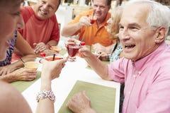 Groupe d'amis supérieurs appréciant des cocktails dans la barre ensemble Photo stock