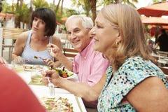 Groupe d'amis supérieurs appréciant le repas dans le restaurant extérieur Image stock