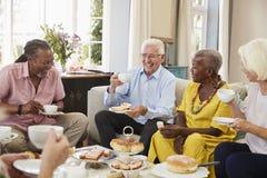Groupe d'amis supérieurs appréciant le thé d'après-midi à la maison ensemble photos stock