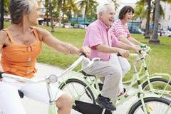 Groupe d'amis supérieurs ayant l'amusement sur le tour de bicyclette Image stock
