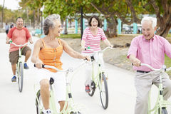 Groupe d'amis supérieurs ayant l'amusement sur le tour de bicyclette Photo stock