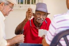 Groupe d'amis supérieurs heureux jouant des cartes et rire Photo stock