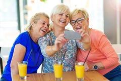 Groupe d'amis supérieurs prenant un selfie Image stock