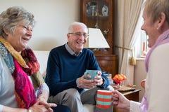 Groupe d'amis supérieurs se réunissant à la maison pour le café Photographie stock