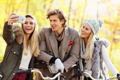 Groupe d'amis sur des vélos dans la forêt pendant le temps de chute Image stock