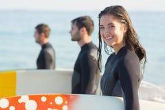 Groupe d'amis sur des wetsuits avec une planche de surf un jour ensoleillé Images stock