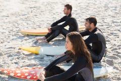Groupe d'amis sur des wetsuits avec une planche de surf un jour ensoleillé Photos stock
