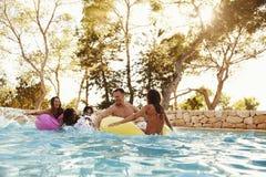 Groupe d'amis sur Inflatables dans la piscine extérieure Image libre de droits
