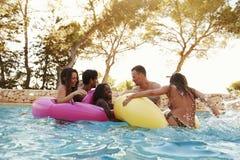 Groupe d'amis sur Inflatables dans la piscine extérieure Images stock