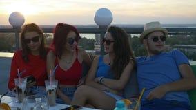 Groupe d'amis sur la barre de dessus de toit ayant une causerie et appréciant une boisson banque de vidéos