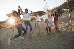 Groupe d'amis sur la plage ayant l'amusement Photos libres de droits