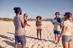 Groupe d'amis sur la plage jouant avec la boule Image libre de droits