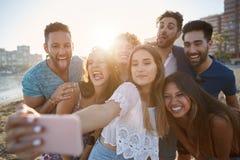Groupe d'amis sur la plage prenant le selfie ayant l'amusement Photo stock