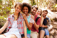 Groupe d'amis sur la promenade équilibrant sur le tronc d'arbre dans la forêt Photos stock