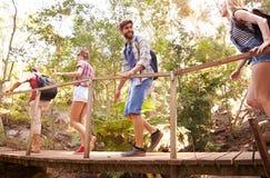 Groupe d'amis sur la promenade croisant le pont en bois dans la forêt Photo stock