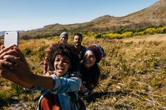 Groupe d'amis sur la promenade prenant le selfie dans la campagne Photos libres de droits