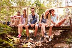 Groupe d'amis sur la promenade se reposant sur le pont en bois dans la forêt Photographie stock libre de droits