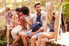 Groupe d'amis sur la promenade se reposant sur le pont en bois dans la forêt Image stock
