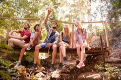 Groupe d'amis sur la promenade se reposant sur le pont en bois dans la forêt Photo libre de droits