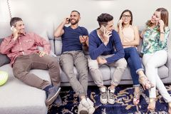 Groupe d'amis sur le divan au téléphone en même temps Photographie stock libre de droits