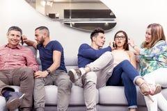 Groupe d'amis sur le divan au téléphone en même temps Photos stock