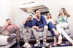 Groupe d'amis sur le divan au téléphone en même temps Photo libre de droits