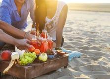 Groupe d'amis tenant des boissons au pique-nique d'été Photos libres de droits