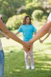 Groupe d'amis tenant des mains en parc Photo stock