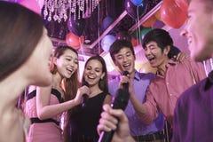 Groupe d'amis tenant des microphones dans une boîte de nuit et chantant ensemble le karaoke Photo libre de droits