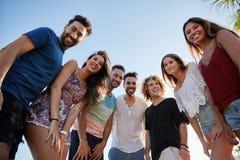 Groupe d'amis tenant ensemble le sourire d'extérieur Photographie stock libre de droits