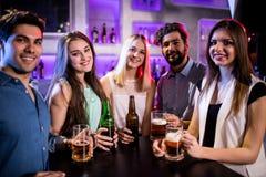 Groupe d'amis tenant la bouteille à bière et le verre de bière au compteur de barre Photographie stock
