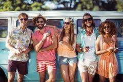 Groupe d'amis tenant le téléphone portable et le sourire Photographie stock