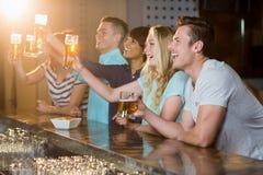 Groupe d'amis tenant le verre de bière en partie Photo stock