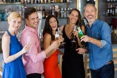 Groupe d'amis tenant le verre de la cannelure et de la bouteille de champagne Image libre de droits