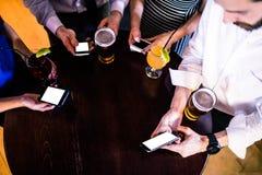 Groupe d'amis textotant et ayant une boisson Image stock